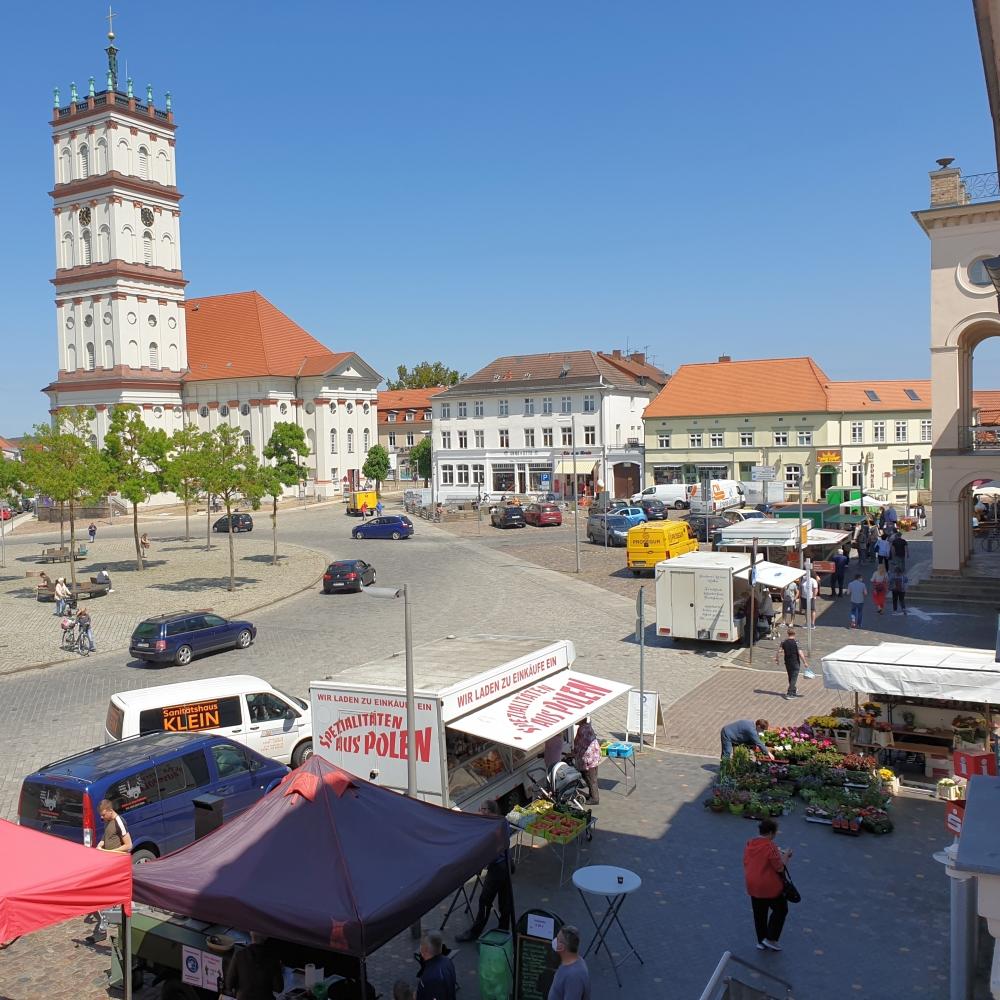 Neustrelitz, beim Rathaus mit Treiben auf dem Wochenmarkt.